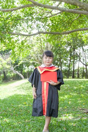 Happy Asian school kid graduate in graduation cap. Zdjęcie Seryjne