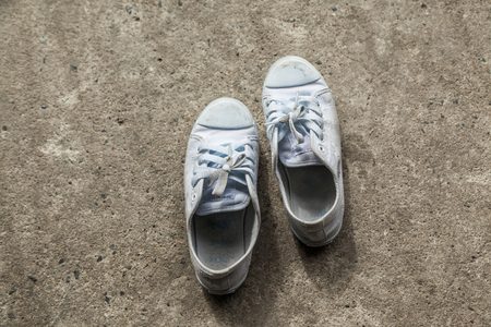 Vintage shoes, White Sneakers on Floor concrete.