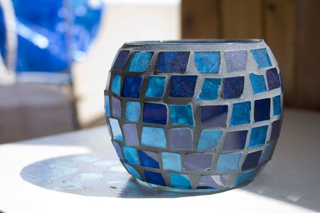 This is a blue mosaic vase made of glass photo