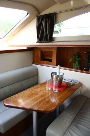 This is an interior of yacht with the bottle of champagne and two glasses photo