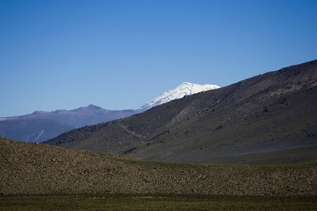 viewed from behind: Snow peak of Ampato volcano viewed from behind the closest hills