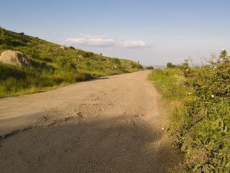 caucasus: Dirty rural road, green meadow, blue sky - Georgia, Caucasus,