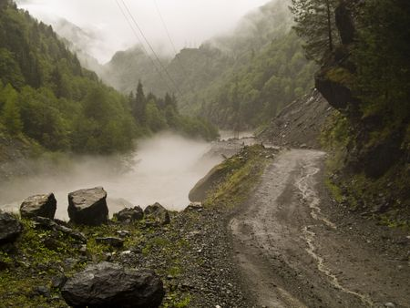 clay stone road in jungle: Foggy rainy day in Georgia. Route to Mestia Stock Photo