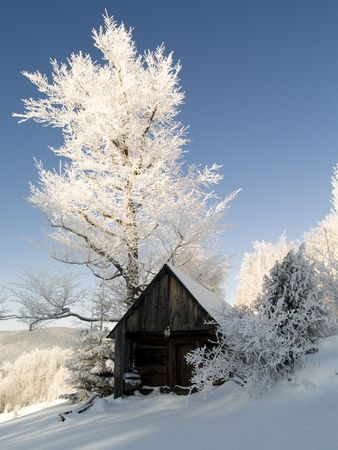Small wooden cottage. Blue sky and a lot of white snow. Stock Photo