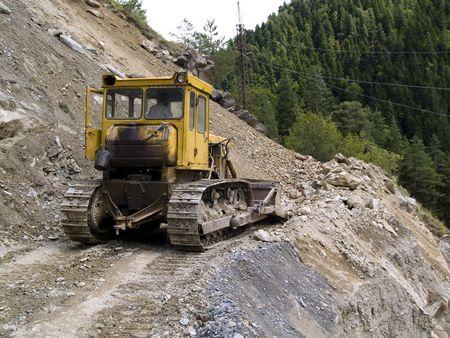 Yellow bulldozer on the small mounatin path in Caucasus mountain