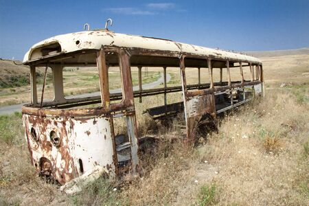downcast: Old bus on the meadow in background small route. Armenia Stock Photo