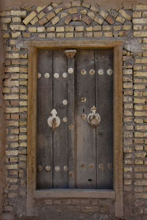 Wooden door brick wall. Yazd in Iran photo