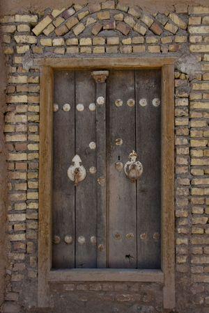 Wooden door brick wall. Yazd in Iran photo