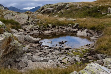 Cloudy day in Pyrenees - Andorra. Puddle on the meadow. photo