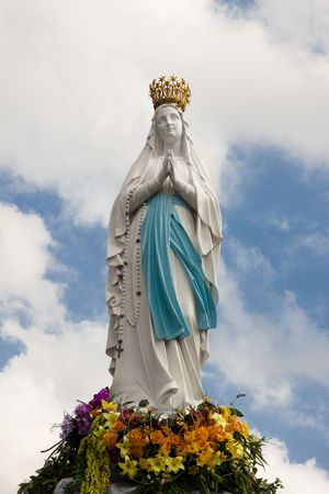 Big figure of the Madonna in Lourdes - France. Cloudy day Standard-Bild