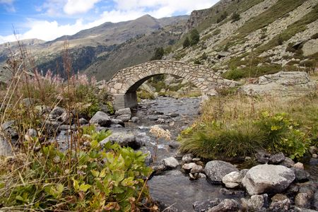 Blue sky, summer day in Pyrenees. Stone bridge over rapid river. photo