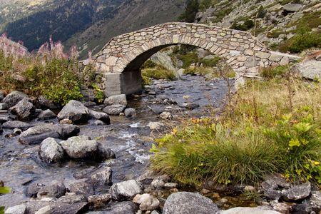 Stone bridge over beautiful river in summer - Pyrenees. Andorra.