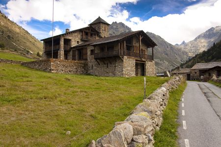 Big stony house in Pyrenees mountain - Andorra summer day, blue sky.