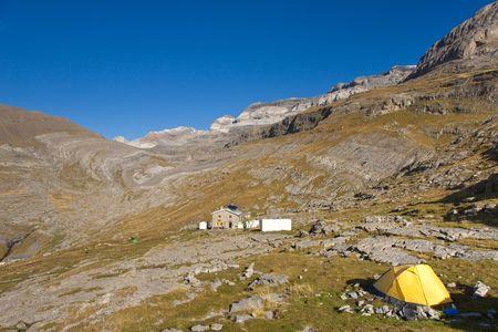 perdido: Yellow tent and in background refuge Goriz and monte Perdido massif. Ordesa National Park - Spain.