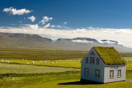 Ancienne ferme avec un toit moussu et typique paysage islandais.