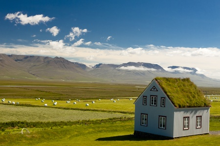 Old farm with mossy roof and typical icelandic landscape.