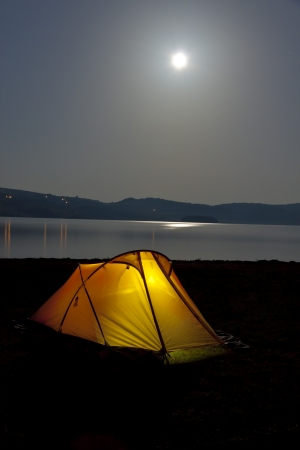 Yellow tent on coast of Vlasinsko lake in Serbia - Balkans at night.