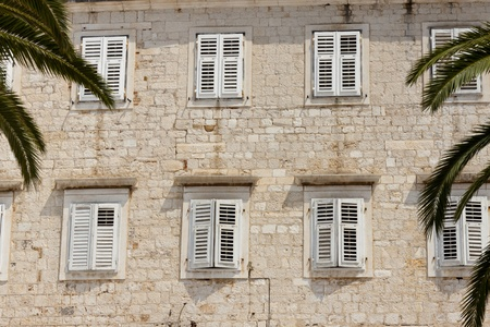 Stony wall and windows with white shutters in Trogir - Croatia  photo