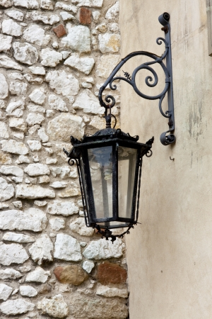 Detail of Benedictine monastery - Street lamp and stony wall. photo