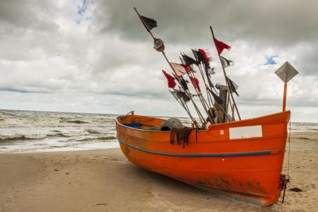 Bateau de p�che sur la plage de sable en jour pluvieux - Rewal, Pologne, Mer Baltique.