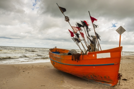 Fishing boat on the sandy beach in rainy day - Rewal, Poland, Baltic sea.