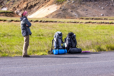 Low budget adventure in Iceland - girl hitchhiking by the roadside  Stock Photo - 17287829