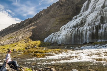 Dynjandi waterfall and women on the stone - Iceland, Westfjords  photo