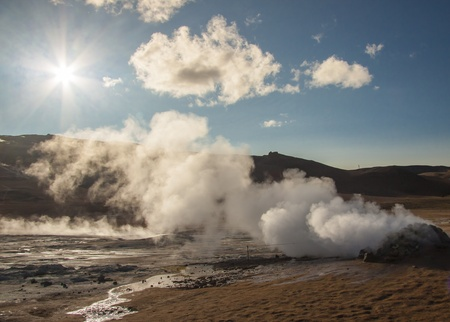 Steam at high pressure of the Sulphurous hill Namafjall in Iceland  Blue sky with sun  photo