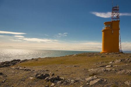 Small orange lighthouse on Hvalnes - coast of Iceland. photo