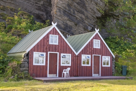 Two wooden red cottage on camping - Vik, Iceland. photo
