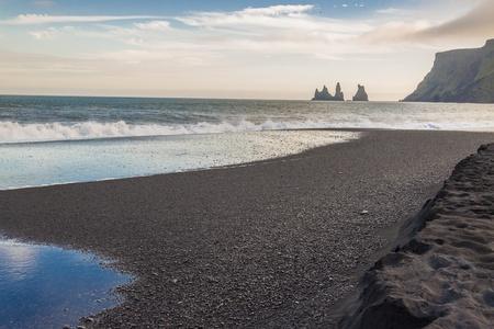 Beauty dark sandy beach in background Dyrholaey stone - Vik, Iceland. photo