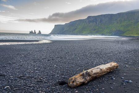 Beauty dark sandy beach in background Dyrholaey stone - Vik, Iceland. Summer sunny day. photo