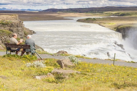 Gullfoss waterfall and two man on the wooden bench - Iceland  Sunny summer day  photo