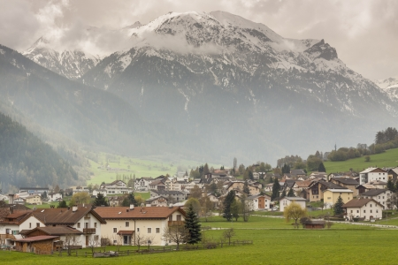 View on Mustair village in background big Alps mountains - Switzerland, Europe. Spring cloudy day.