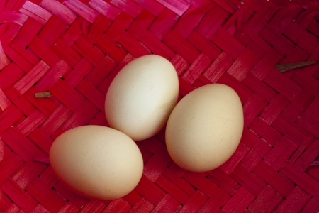 Three big ecological chicken eggs in red wicker basket. photo
