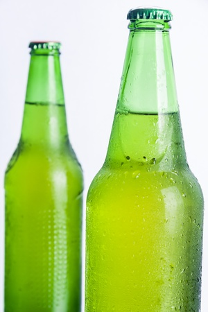 Two wet bottle with cold beer on white background. photo