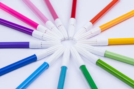 Pallet of colourful markers on white background.