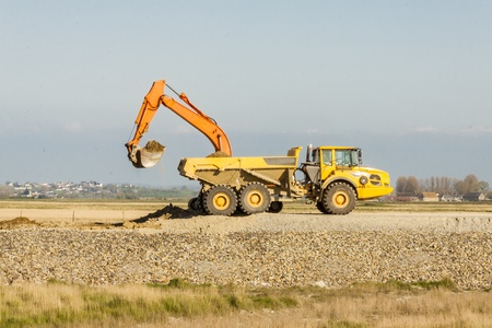 Yellow excavator loading soil on a big truck at mine  photo
