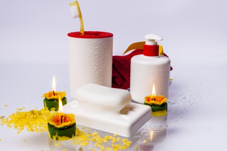 Toothbrushes, soap, liquid soap and red towel on white background. photo