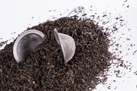 tea filter: Black tea and tea strainer on white background.
