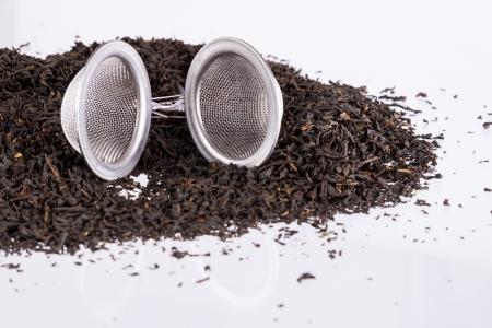 infuser: Black tea and tea strainer on white background.