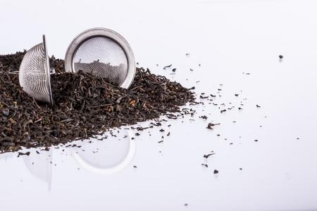 El té negro y el colador de té en el fondo blanco. Foto de archivo