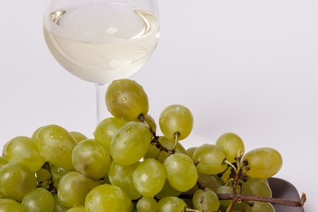 White grapes with a glass of white wine on white background photo