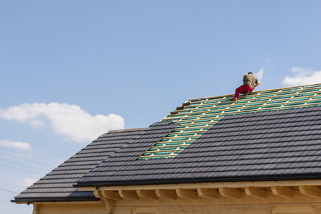 Roofer working on the top of the unfinished roof