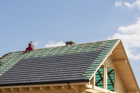 未完成の屋根上の屋根葺き職人 写真素材
