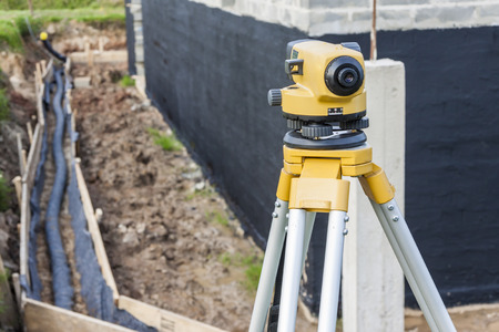 surveyor: Surveyor equipment optical level at construction site