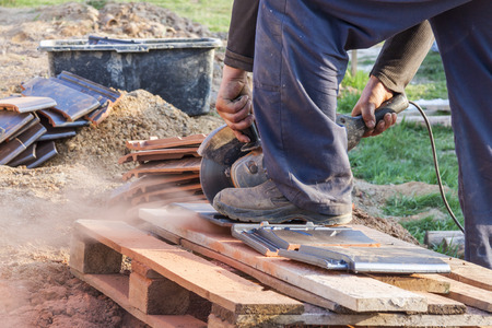 cut off saw: Worker using a hand circular saw to cut a roof-tile