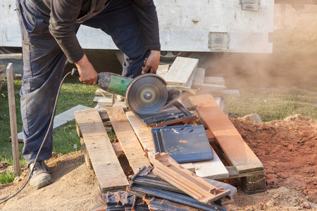 tile cutter: Worker using a hand circular saw to cut a roof-tile