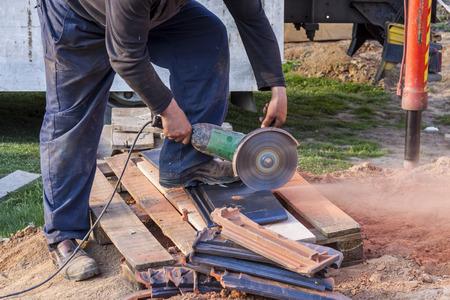 rooftile: Operaio con una sega circolare a mano per tagliare una tegola