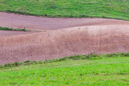 ploughed: Green meadow and ploughed brown field.
